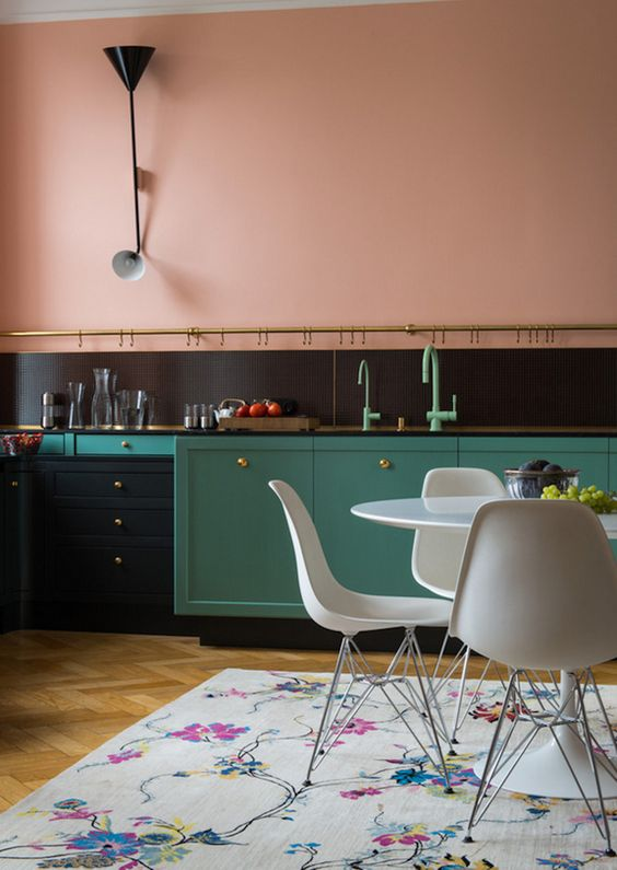 kitchen without upper cabinet, wooden floor, flowery rug, green cabinet, white modern dining table set, black backsplash, pink painted wall, black cabinet