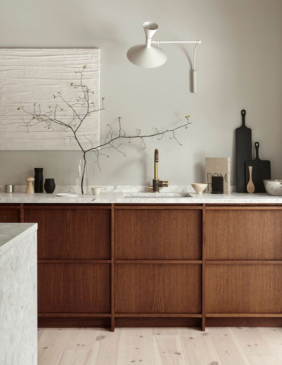 kitchen, wooden floor, darker wooden cabinet, beige wall, marble counter top and island, white sconces