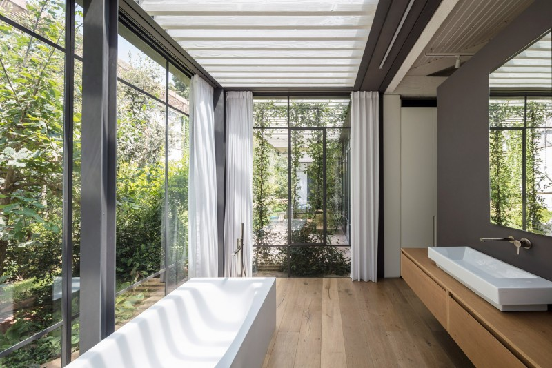 large bathroom, wooden floor, large glass walls, pergolla ceiling, wooden floating vanity, white sink, mirror, white wall