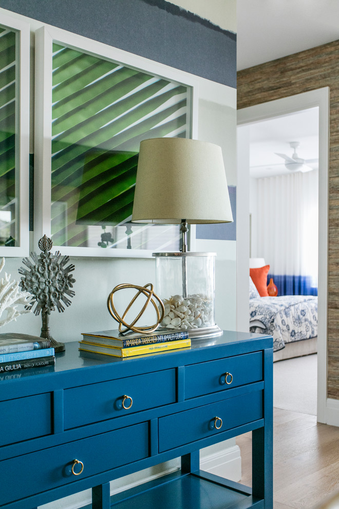 large glass table lamp artwork blue entryway table with drawers wooden floor golden cabinet hardware books table decoration ceiling fan accent walls