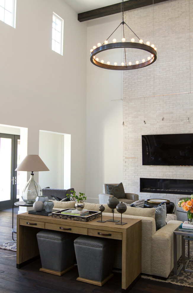 large glass table lamp circle chandelier modern fireplace white brick wall wooden console grey stools sofas grey armchairs pillows side tables area rug