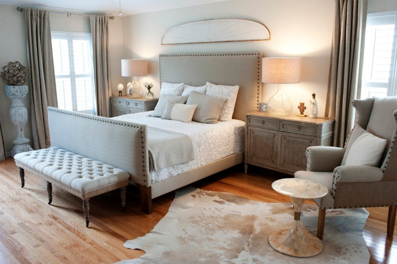 large glass table lamp cowhide rug grey bed headboard tufted bench grey armchair pedestal table wooden nightstands curtains wooden floor pillows