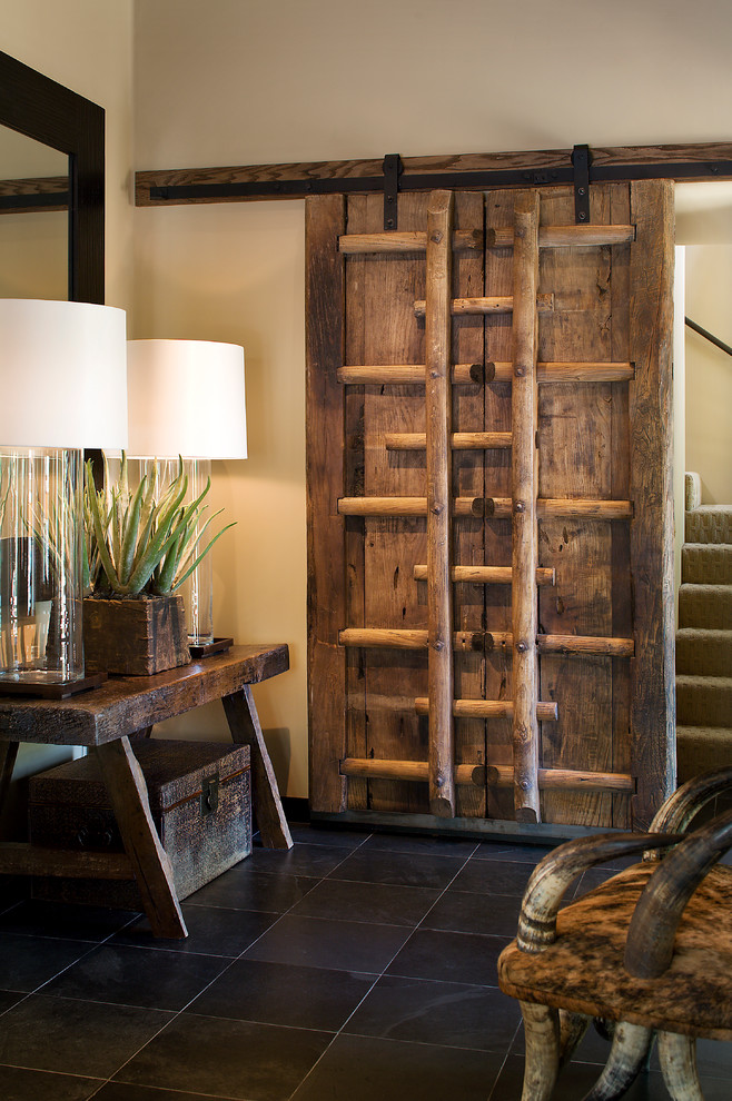 large glass table lamp fabricated wooden door beige walls black floor tiles staircase antique chair wooden console table rustic trunk wall mirror