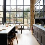 Large Kitchen With Wooden Floor, Black Wooden Cabinet And Island With White Marble Top, Black Stool, Open Brick Wall, ,glass Wall, Wooden Chair And Table