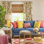 Living Room, Beige Wall, Blue Sofa, Colorful Pillows, Maroon Chairs, Glass Nesting Tables, White Orange Ikat Patterned Rug, Colorful Curtain, Yellow Table Lamp