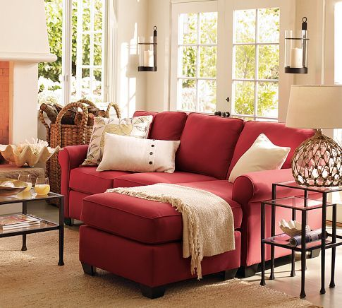living room, brown rug, red sofa, white pillows, glass coffee table, white walls, sconce, glass side table