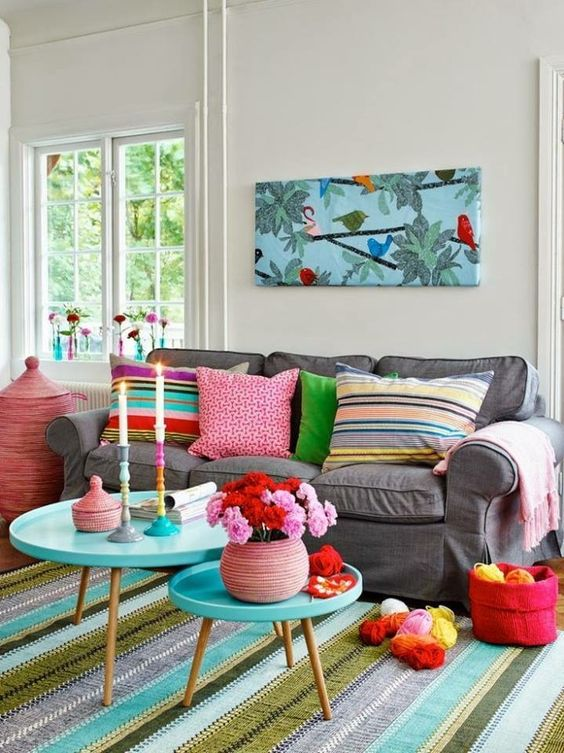 living room, colorful rug, gery sofa, colorful pillows, round tray nesting table, white wall,