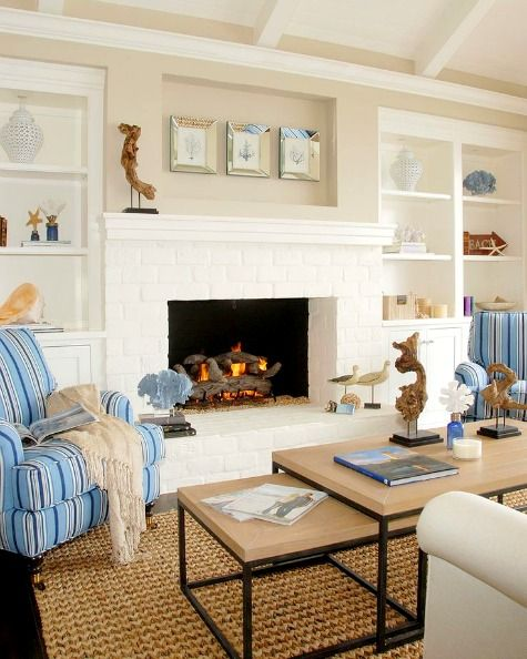 living room, rattan rug, wooden coffee tables, white fireplace, blue stripes chairs, built in shelves