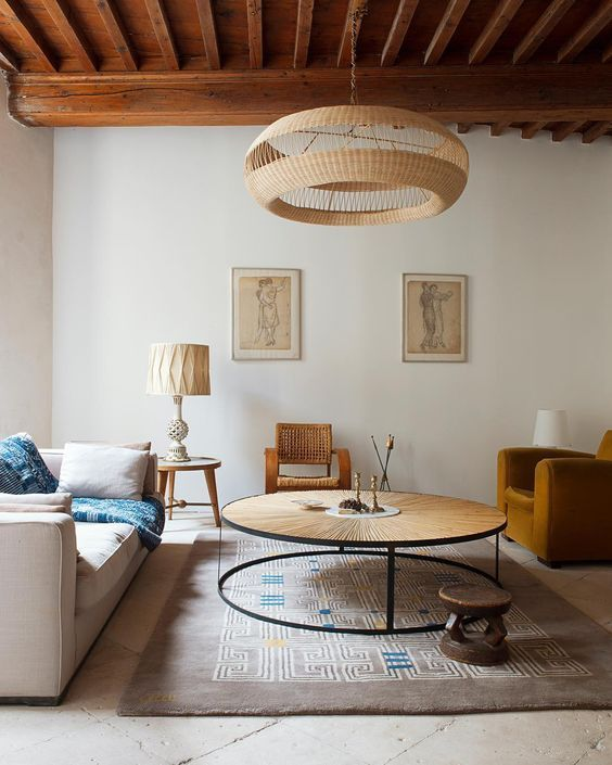 living room, white floor, rug, white wall, wooden ceiling, off white sofa, mustard chair, round coffee table with wooden top, natural pendant, wooden rattan chair, table lamps