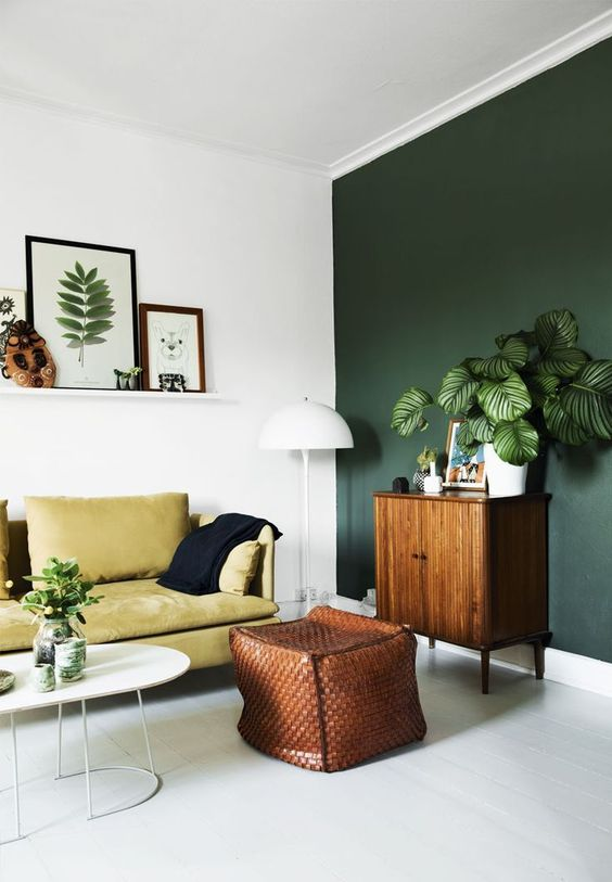 living room, white floor, white wall, green wall, green sofa, white coffee tbale, leather woven ottoman, wooden cabinet, white floor lamp, white floating shelves