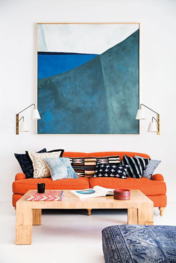 living room, white floor, white wall, wall painting, white sconces, orange sofa, wooden coffee table, blue ottoman