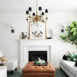 Living Room, White Wall, White Fireplace, Modern Chandelier, White Sofa And Chairs, Brown Ottoman For Coffee Table, Green Rug, Plants, Sconces