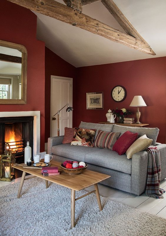 living room, white wooden floor, grey rug, grey sofa, wooden coffee table, dark red wall, white fireplace, wooden beam, wooden console table