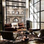 Living Room With Wooden Floor, Rug, Dark Chairs, Dark Sofa, Large Glass Window, Curtain
