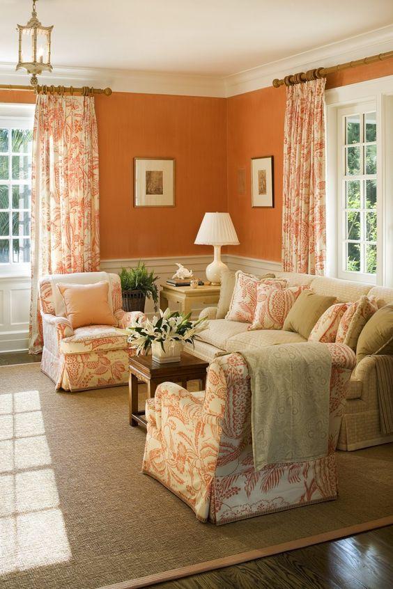 living room, wooden floor, brown rug, beige sofa, white orange chairs, orange painted wall, white molding, windows, curtain