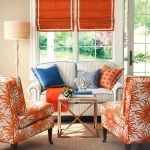 Living Room, Wooden Floor, Brown Rug, White Orange Chairs, White Sofa, Off White Wall, Orange Roman Shades, Glass Windows, Glass Door