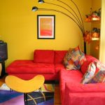 Living Room, Wooden Floor, Colorful Rug, Red Corner Sofa, Yellow Modern Coffee Table, Yellow Painted Wall, Floor Lamp, Yellow Shelves