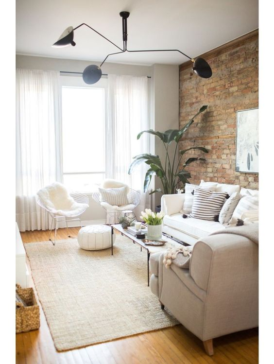 living room, wooden floor, white sofa and chairs, light grey sofa, beige rug, white ottoman, rectangle coffee table, open brick wall, modern pendant, white curtain