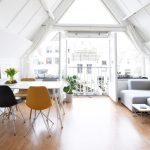 Living Room, Wooden Floor, White Wall, White Sloping Ceiling, Light Grey Sofa, White Table, Mid Century Modern Chairs, Large Glass Windows, Large Glass Doors