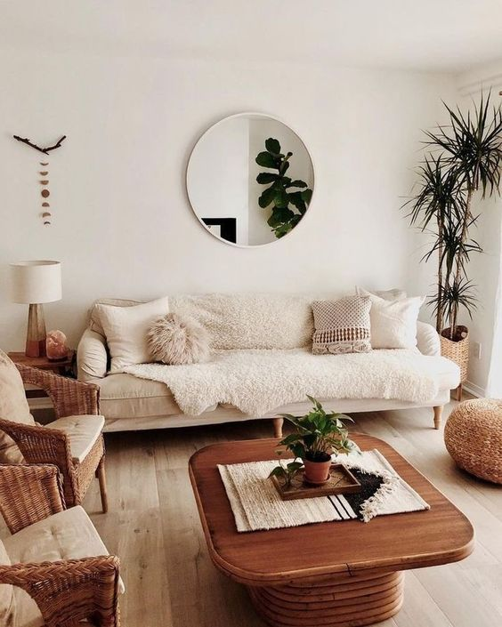 living room, wooden floor, wooden square table, beige sofa, white wall, round mirror, rattan chairs, rattan ottoman