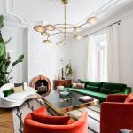 Living Room, Wooden Herringbone Pattern, Rug, Red Chairs, White And Green Sofas, Large Rectangular Black Coffee Table, White Wall, White Ceiling, White Chandelier