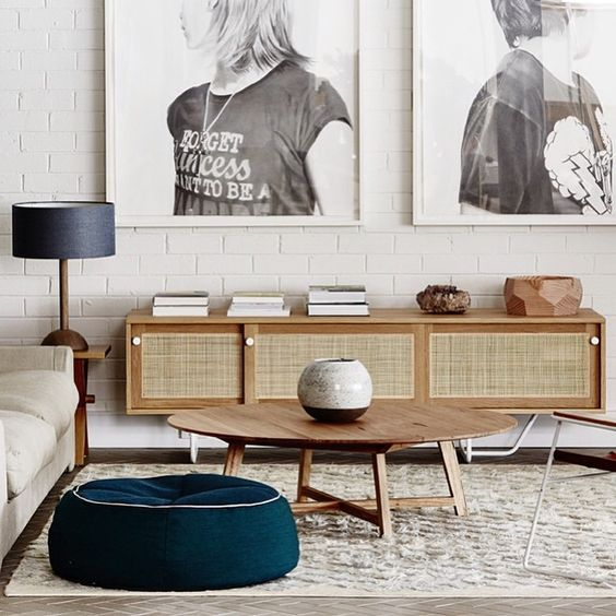 long cabinet with rattan sliding door, white open brick wall, grey floor, rug, wooden round coffee table, light grey sofa, green ottoman, table lamp