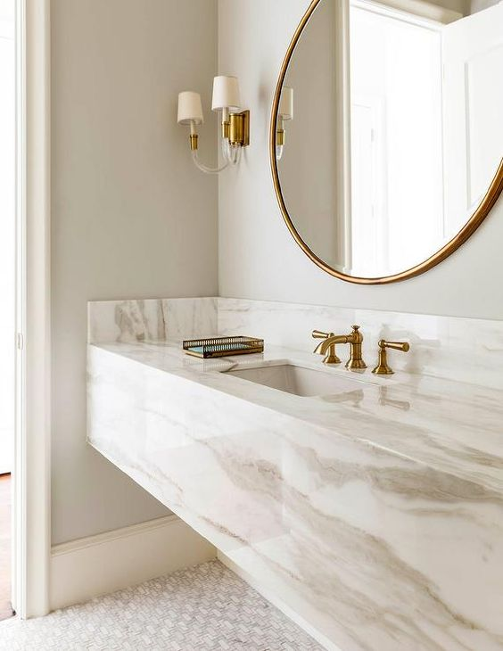 marble floating vanity, light grey wall, sconces, round mirror with golden frame, white flooring