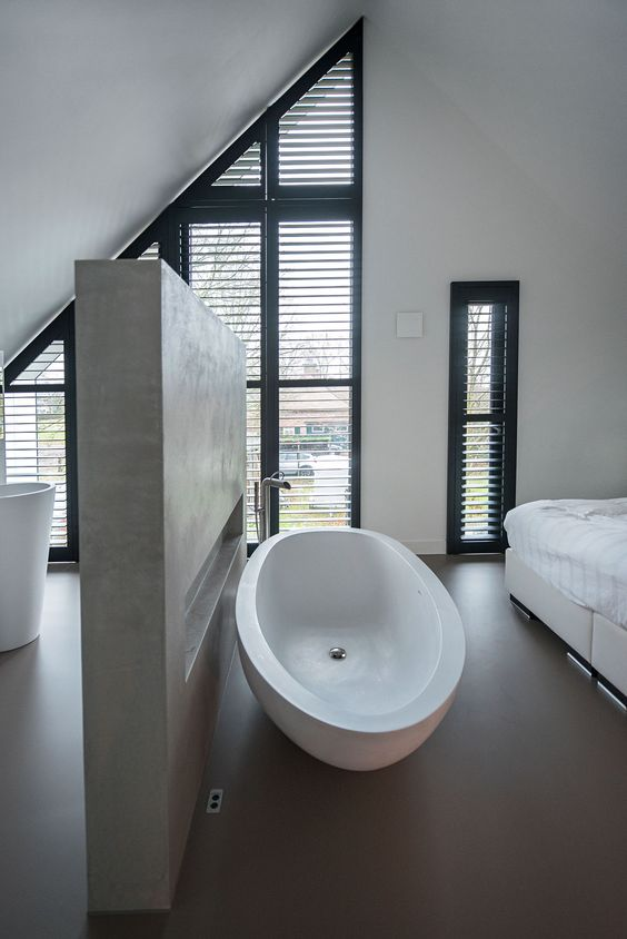 modern bedroom with grey floor, white bed, white tub, grey divider to te bathroom, windows