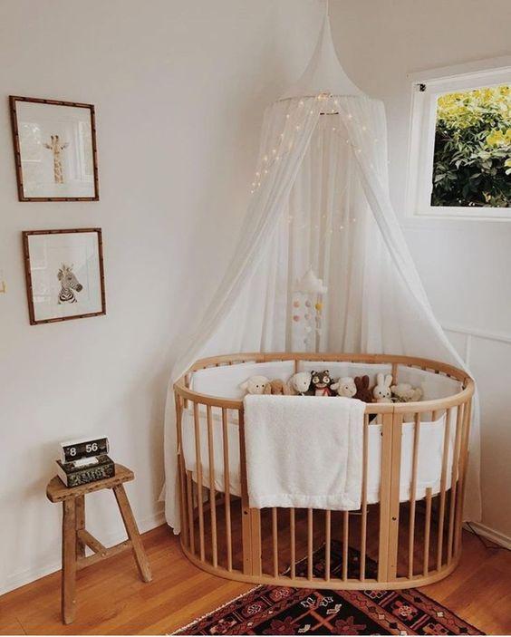 nursery, wooden floor, wooden round crib, white urtain, white wall, animals' pictures, small stool