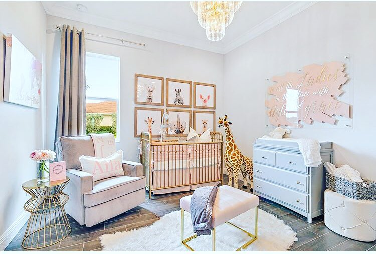 nursery, wooden pattern floor, modern side table, pink chair, pink ottoman, pink crib, blue cabinet, white wall, chandelier, stuffed giraffe, animals' paintings