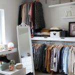 Open Closet In Wooden Floor, White Wall, Floating Rails On Top And Bottom, White Floating Drawers, White Floating Shelves, Mirror, Whit Boxes