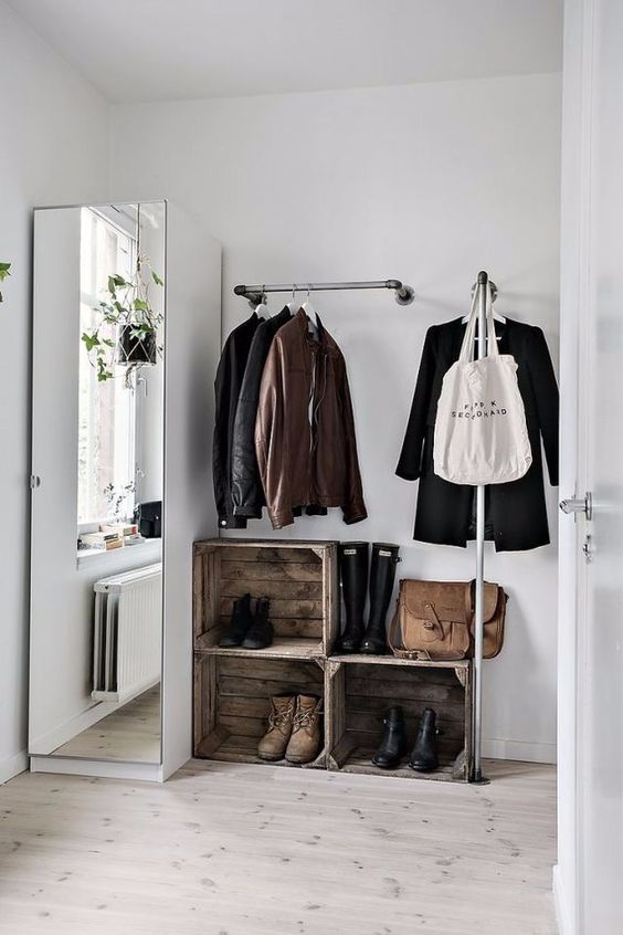 open closet with refurbished boxes, built in rails, white cupboard with tall mirror