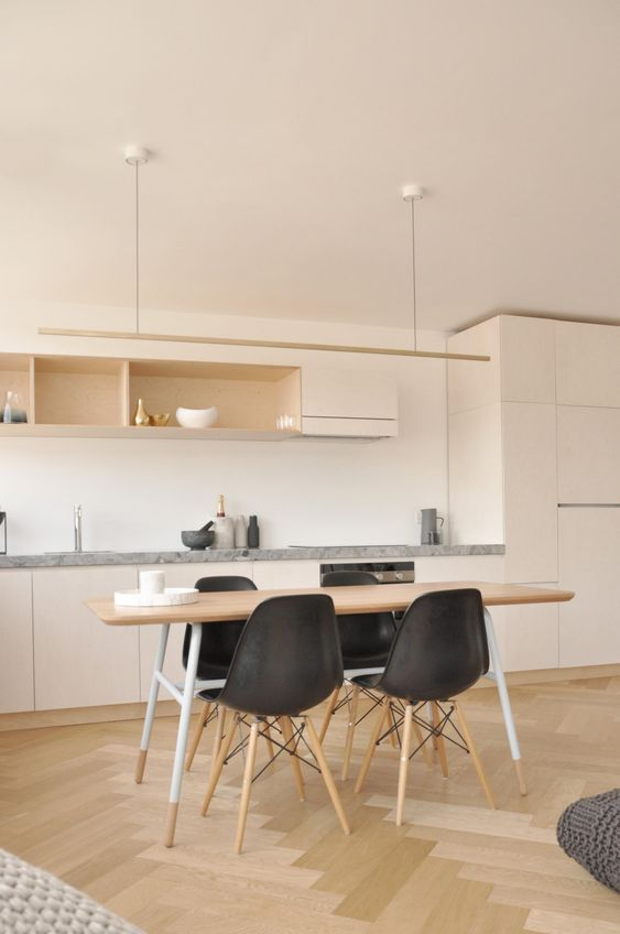 open room, kitchen on beige cabinet, grey marble counter top, wooden dining table, black modern mid century chairs, long pendant