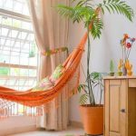 Orange Hammock On Living Room, White Floor Tiles, White Wall, Brown Wooden Cabinet, Beige Curtain, Orang Pot, Pillow,
