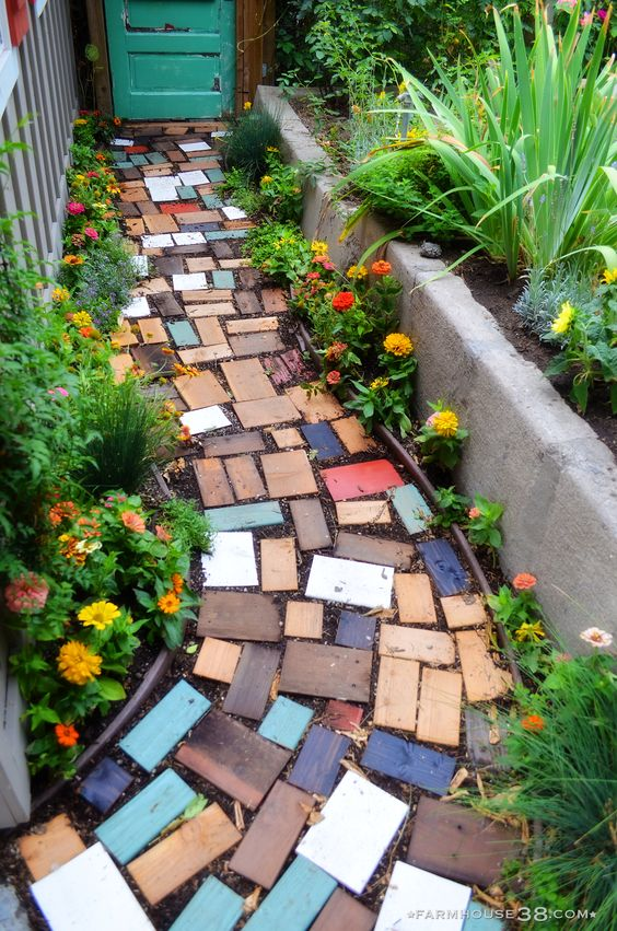 pathway with colorful plain tiles surrounded by flowers and plants