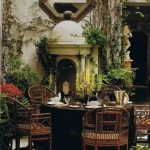Patio, Black And White Flooring Tiles, White Wall, Black Round Table, Wooden Chairs, Vines On The Wall, Plants On The Floor