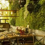 Patio, Wooden Table, Chairs, Round Table, Wooden Chairs, White Wall Tiles, Grass Plants On The Wall, Pendants