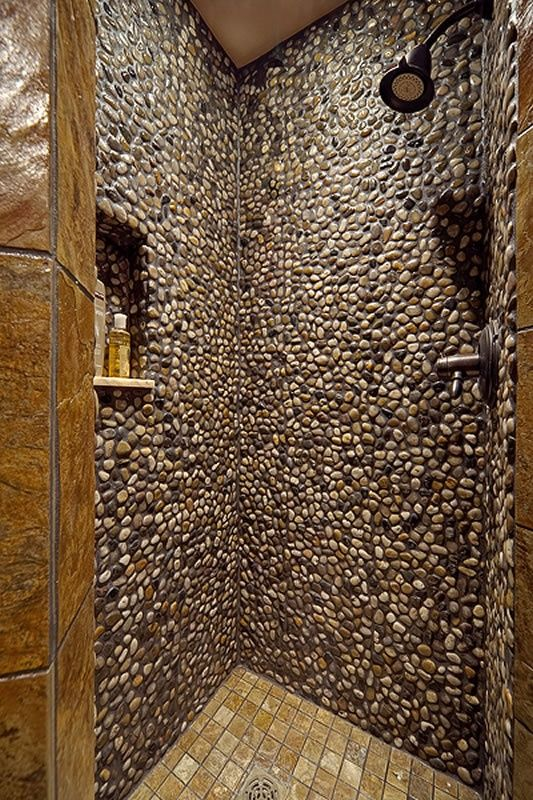 pebbles on the entire shower wall, brown floor tiles, black shower faucet