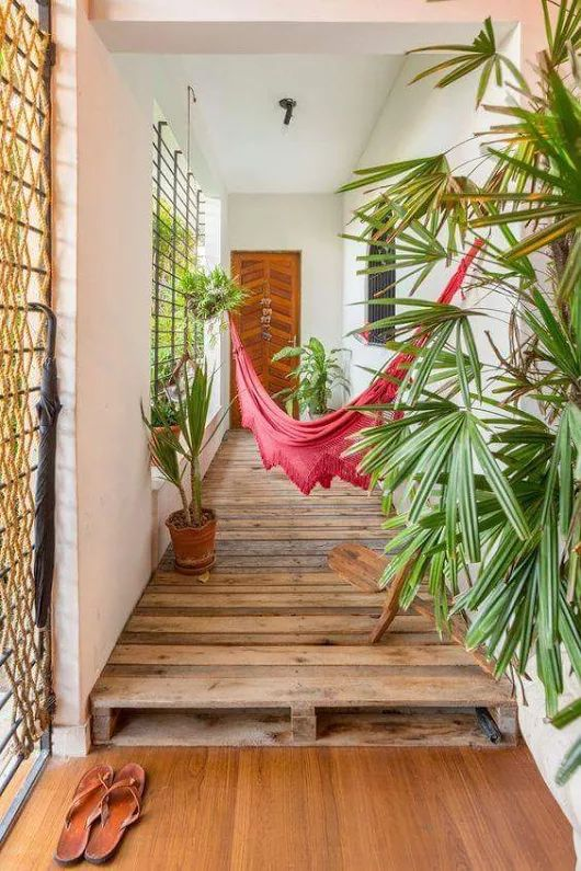 pink hammock with fringe in the hall with wooden platform floor, white wall
