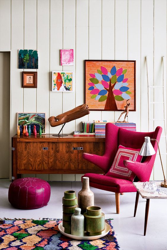 pink unique chair with hollow arm rest, white wall, colorful rug, pink ottoman, white wooden wall, wooden cabinet