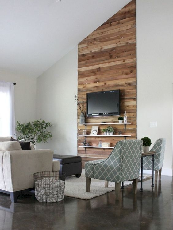 reclaimed wood accent wall on sloping ceiling, dark floor, rug, sofa, chairs, floating shelves, white wall
