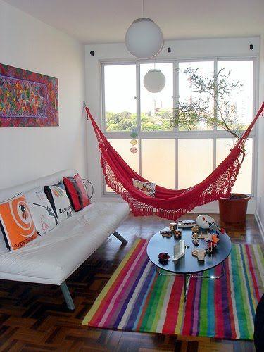 red hammock, wooden herringbone floor, colorful stripes rug, white wall white sofa, white pendant, oval coffee table