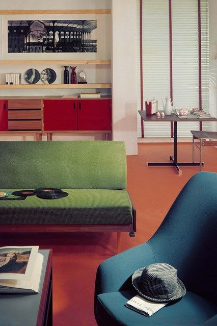 retro living room, brown floor, wooden bench with green cushion, blue chair, red cabinet, floating shelves, blue coffee table