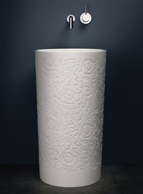 round white carved sink with dark gery wall, silver faucet