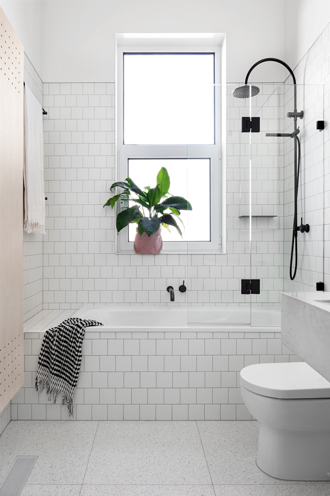 shower components white walls tiles black shower fixtures frosted glass windows indoor plant towel holder built in bathtub toilet white floor tile glass shower door