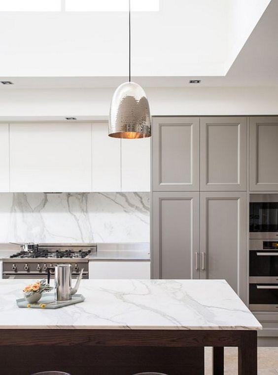 silver pendants, white marble island top, white marble backsplash, white ceiling, white cabinet