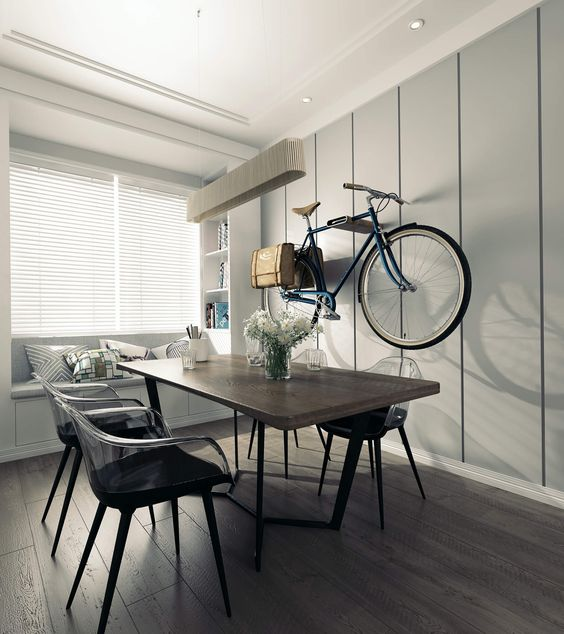 sleek dark square dining table, black chair with acrylic back, wooden floor, light beige wall, bicycle on the wall, window nook