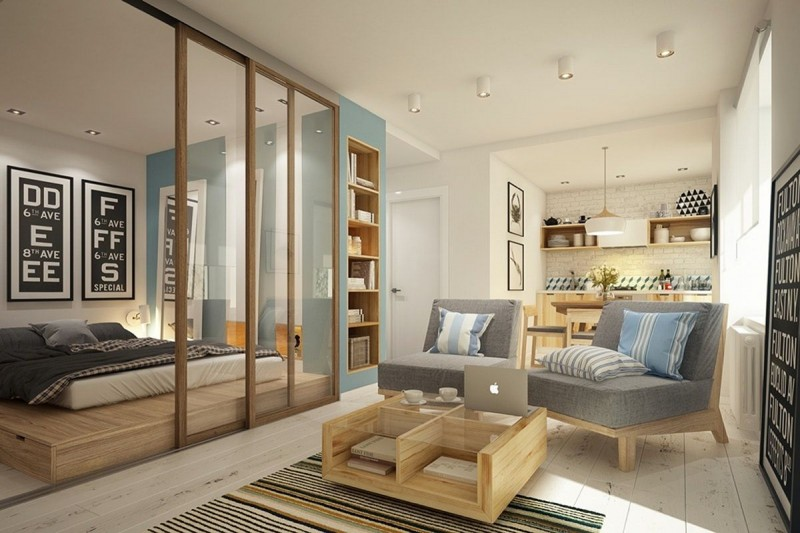 small apartment, light wooden floor, light wooden platform for bed with built in storage, grey chairs, white wall in the kitchen, blue accent wall, wooden coffee table