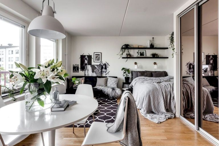 small apartment, wooden floor, white wall, white round table, white chairs, black sofa, white grey bed, black floating shelves