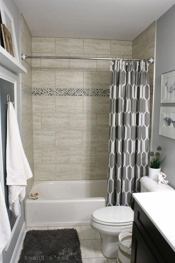 small bathroom with white floor, white toilet, black vanity with white top, grey wall, beige wall tiles on shower, grey geometric curtain